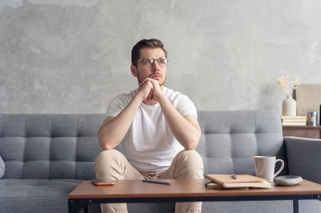 Contemplando al hombre serio sentado en el sofá solo en casa