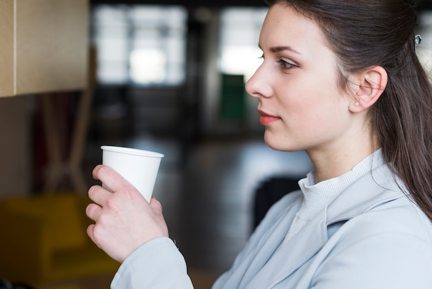 Contemplando atractiva empresaria sosteniendo la taza de café en la oficina