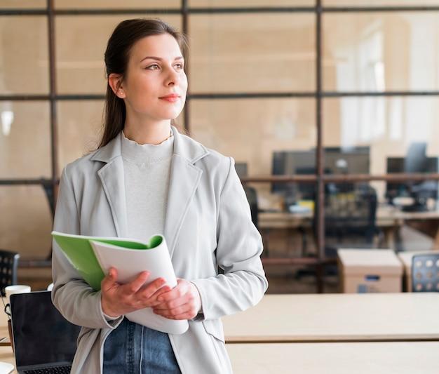 Contemplando hermosa empresaria sosteniendo el libro en el lugar de trabajo