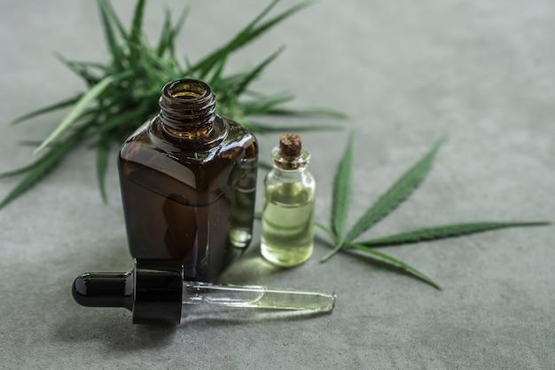 Contenedor de aceite esencial de cannabis con hojas de marihuana