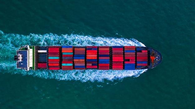 Contenedor de carga, transporte de contenedores, caja de contenedores para importación y exportación, logística comercial y transporte en barco de contenedores en mar abierto, vista aérea.