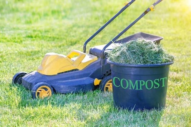 Contenedor de compost lleno de hierba fresca recortando césped en el jardín
