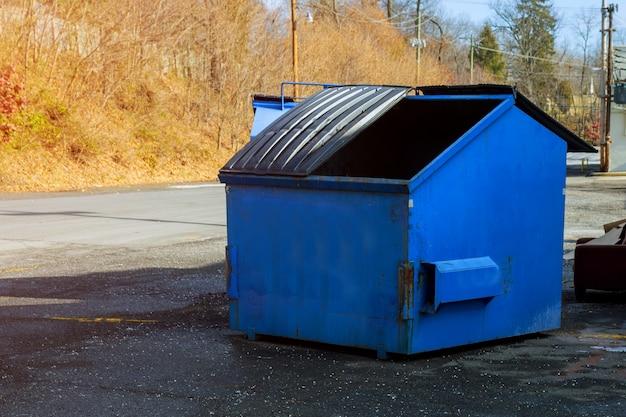 Contenedor de escombros de construcción azul lleno de cubo de basura