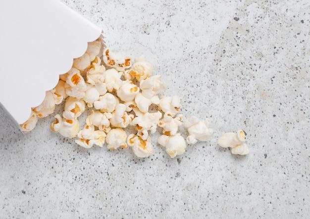 Contenedor de papel con palomitas de maíz saladas frescas sobre fondo de piedra