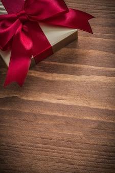 Contenedor presente de oro brillante envuelto en tablero de madera vintage