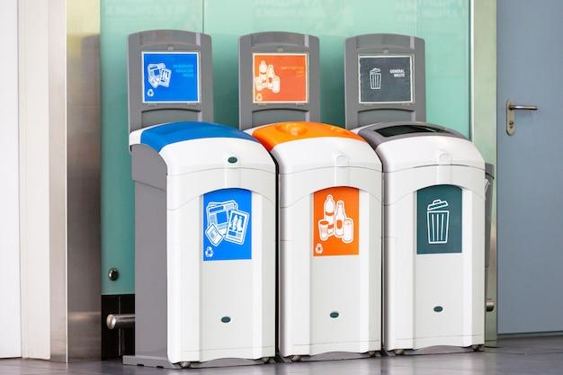 Contenedores de basura para diferentes basuras: plástico, botellas vacías, periódicos, papel de revista y desechos generales.