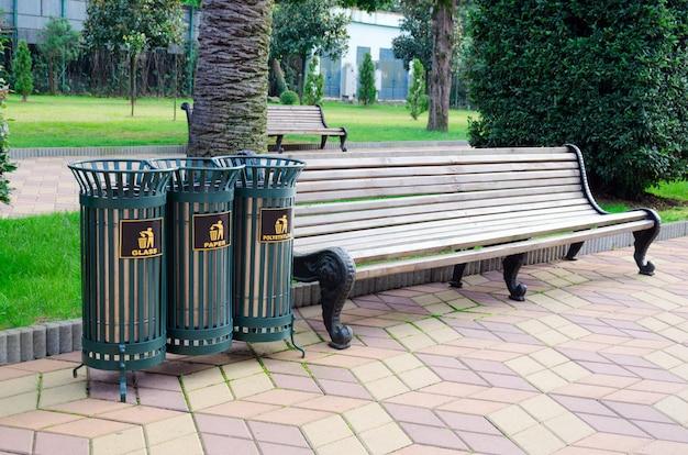 Contenedores de basura de hierro para clasificar la basura en un parque de la ciudad junto a un banco.