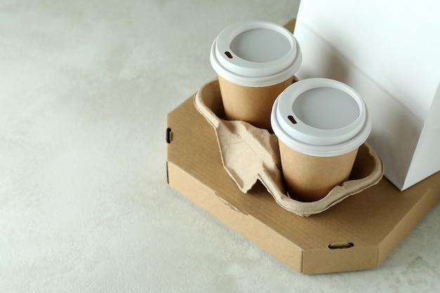 Contenedores de entrega de comida para llevar en mesa con textura blanca