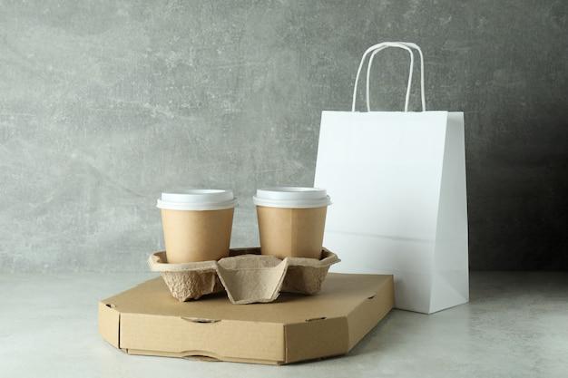 Contenedores de entrega de comida para llevar en la mesa con textura blanca