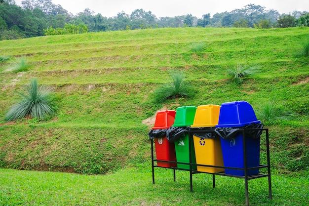 Contenedores multicolores separados sobre un gran campo verde