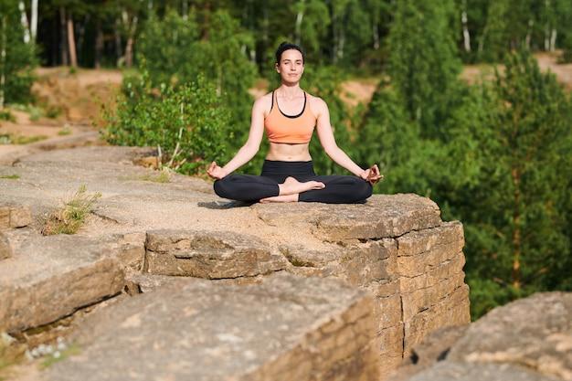 Contenido atractivo chica flexible sentada con las piernas cruzadas y las manos en mudra de rodillas, mujer disfrutando de la meditación al aire libre