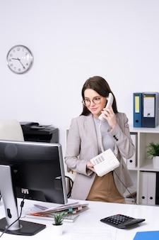 Contenido atractivo joven empresaria en vasos de pie en el escritorio y hablando por teléfono en la oficina