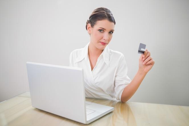 Contenido bonita empresaria de compras en línea usando la computadora portátil