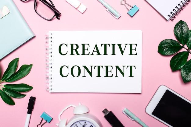 Contenido creativo está escrito en un cuaderno blanco sobre un fondo rosa rodeado de accesorios comerciales y hojas verdes