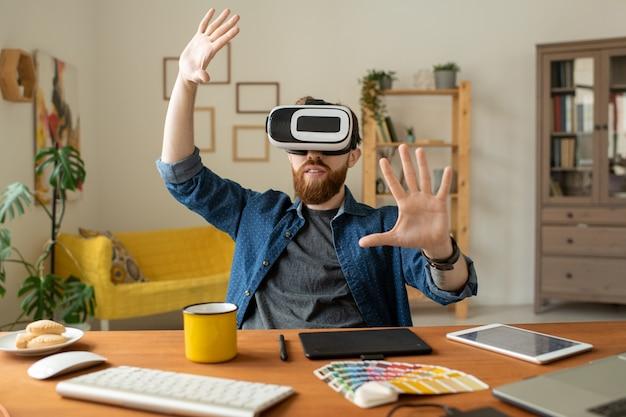 Contenido curioso hombre barbudo sentado en el escritorio en la oficina en casa y gesticulando con las manos mientras prueba una nueva aplicación en gafas de realidad virtual
