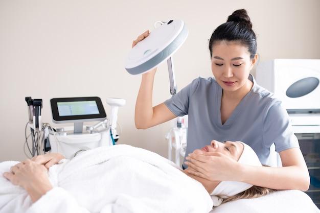 Contenido esteticista asiática tocando la cara del cliente maduro en la mesa de masaje y ajustando la lámpara antes del procedimiento cosmético