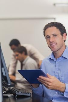 Contenido estudiante masculino con su tableta sentado en clase de informática