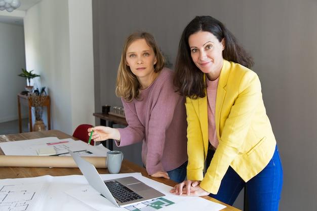 Contenido femenino arquitecto y cliente discutiendo el diseño de la casa