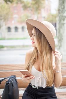 Contenido hermosa mujer sentada en el banco en verano