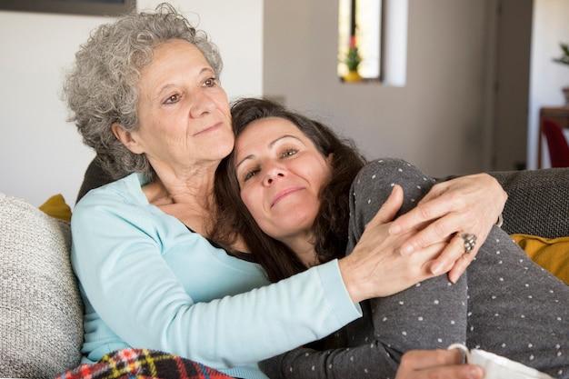 Contenido de hija de mediana edad abrazada por madre descansando en casa.