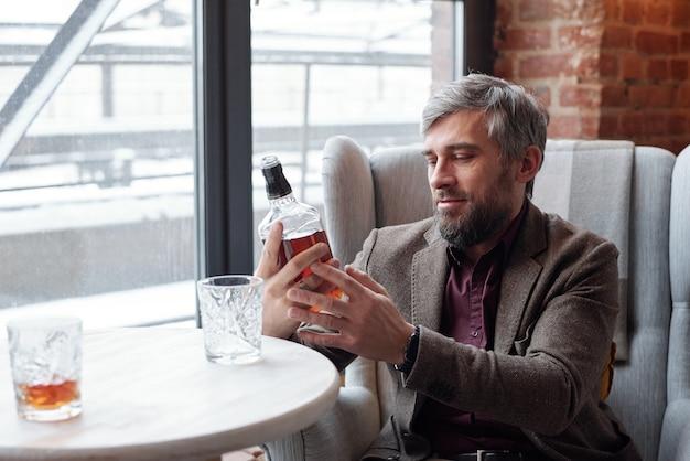 Contenido hombre barbudo de mediana edad en elegante chaqueta sentado en un sillón y mirando con botella de whisky