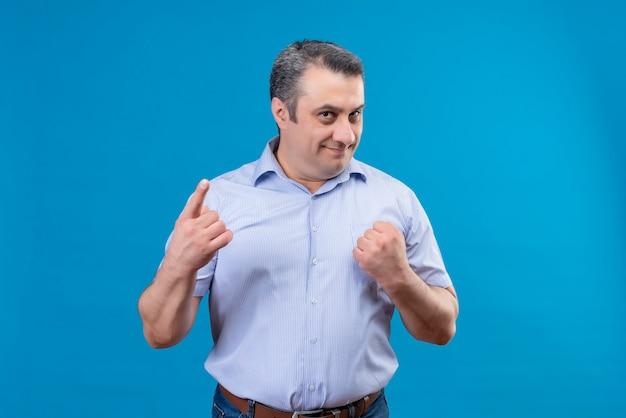 Contenido hombre de mediana edad en camisa a rayas sosteniendo el puño cerrado y apuntando con el dedo índice en un espacio azul