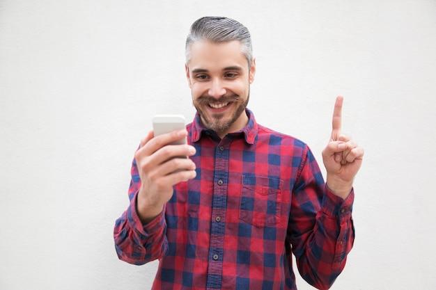 Contenido hombre con teléfono inteligente apuntando hacia arriba con el dedo