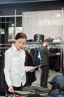 Contenido joven empleada de la tienda de ropa en camisa blanca con tableta mientras comprueba la visualización de prendas en la tienda