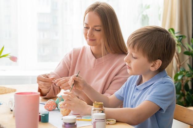 Contenido joven madre e hijo sentados a la mesa y usando gouache para pintar huevos en pascua