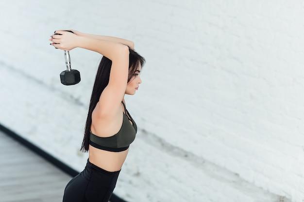 Contenido joven modelo morena en ropa deportiva negra haciendo ejercicio con pesas