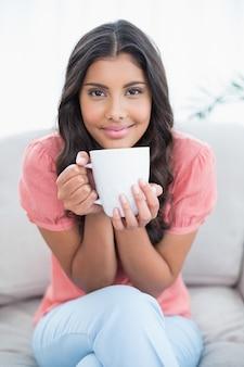 Contenido morena linda sentada en el sofá con taza