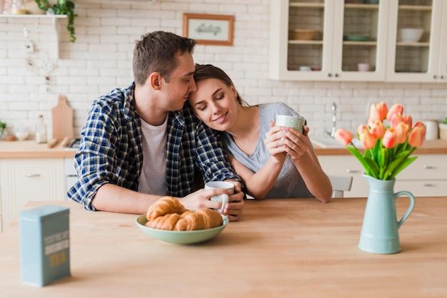 Contenido pareja uniéndose a la mesa y disfrutando del té