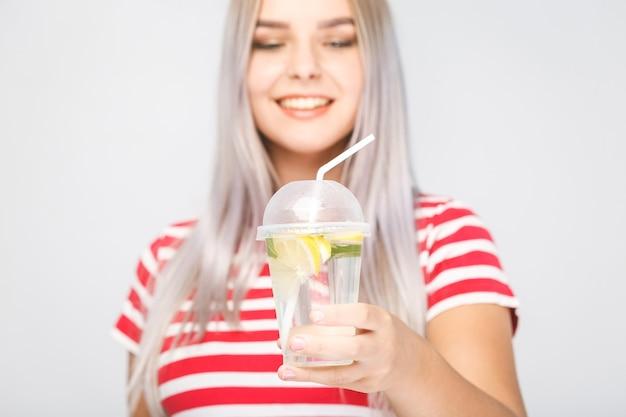 Contenido de salud, personas, comida, deportes, estilo de vida y belleza - mujer joven sonriente con un vaso de agua con limón