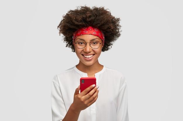 Contenido sonriente modelo femenino con expresión positiva tiene moderno teléfono inteligente rojo, navega páginas web en internet, charla en redes sociales con amigos. concepto de personas, tecnología y comunicación