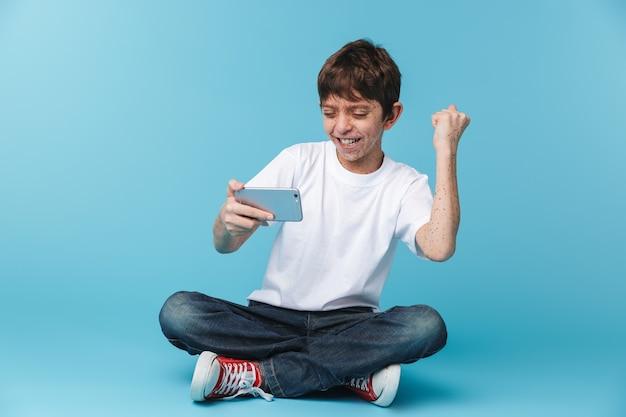 De contento niño morena con pecas vistiendo camiseta blanca casual sosteniendo y usando el teléfono inteligente mientras está sentado en el piso aislado sobre la pared azul
