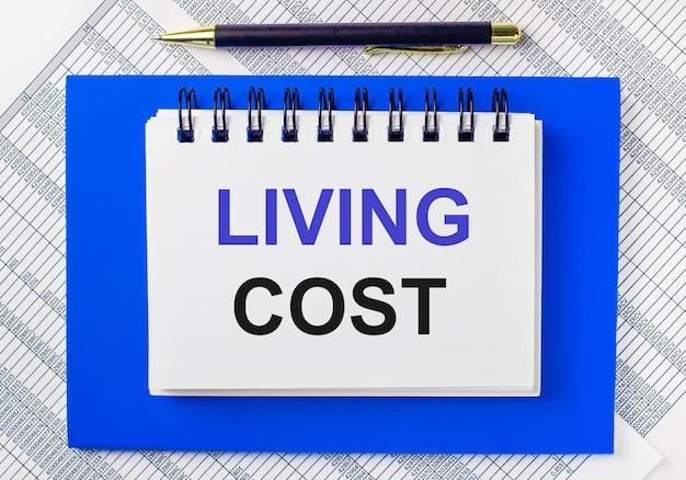 En el contexto de los informes en el escritorio, un bloc de notas azul. tiene un bolígrafo y un cuaderno blanco con el texto coste de vida. concepto de negocio