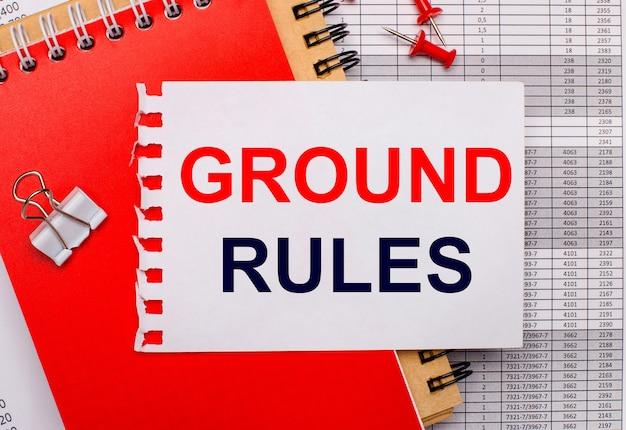 En el contexto de los informes, hay cuadernos de notas rojos y marrones, un clip de papel blanco, botones rojos y una hoja de papel blanca con el texto reglas de base. concepto de negocio