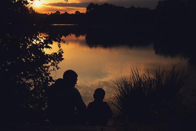 Contorno de un niño con papá al atardecer en el lago