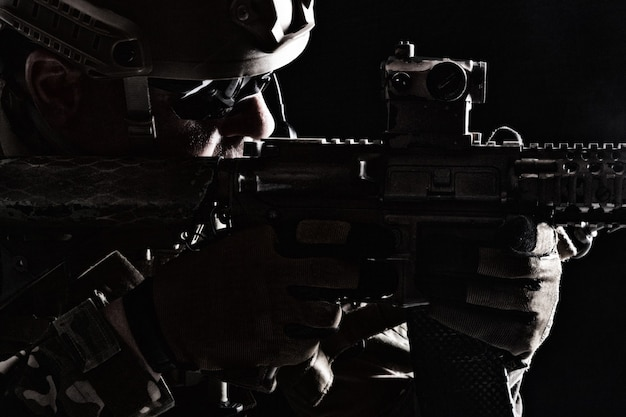 Contorno de retroiluminación retrato de soldado de las fuerzas especiales en uniformes apuntando armas, retrato en primer plano en negro