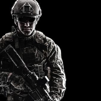 Contorno de retroiluminación retrato de soldado de las fuerzas especiales en uniformes con armas, retrato en negro