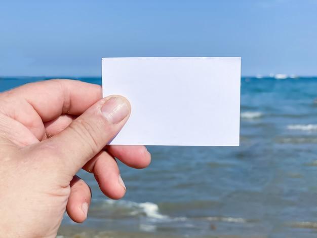 Contra el fondo del mar, la mano de un hombre sostiene una tarjeta de presentación blanca