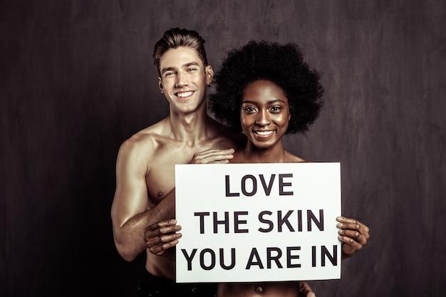 Contra el racismo. encantado de feliz pareja sonriéndole mientras participa en el movimiento social contra el racismo