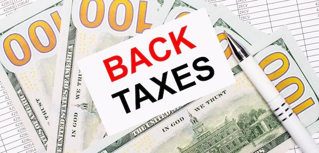 Contra la superficie de informes y dólares: un bolígrafo blanco y una tarjeta con el texto impuestos atrás