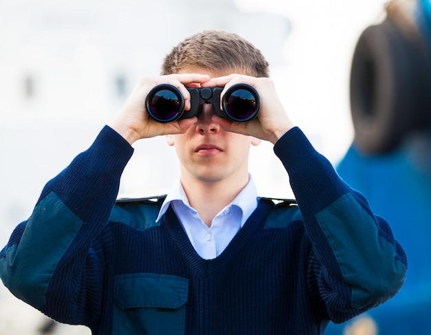 Contramaestre con binoculares cerca del barco.