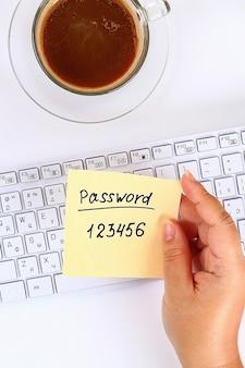 La contraseña en la etiqueta es una nota en el escritorio blanco al lado de la taza de café y el teclado.