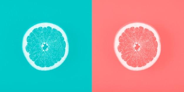 Contraste de fondo azul y coral con rodaja de pomelo.