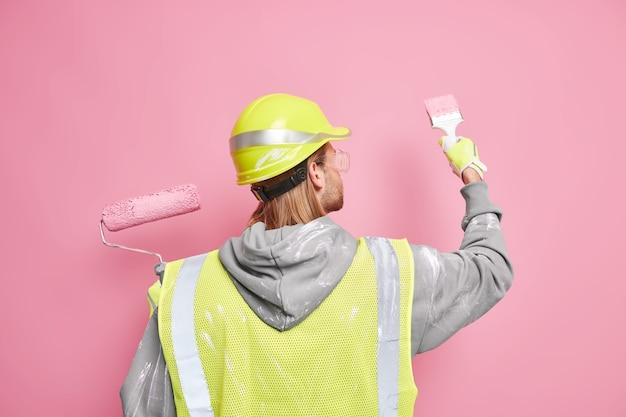Contratista de construcción ocupado se encuentra detrás pinta la pared con un cepillo vestido con uniforme de trabajo y casco utiliza herramientas para la reparación. arquitecto calificado repara la construcción. trabajador manual. día laboral