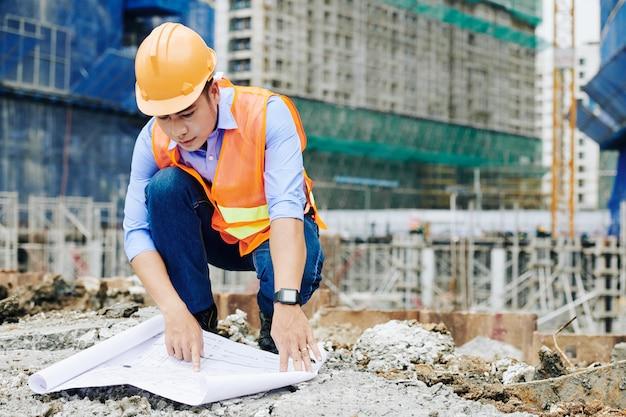 Contratista examinando planos de construcción