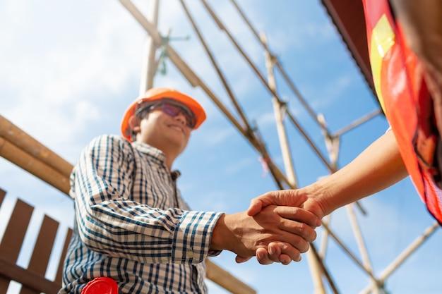Contratista del ingeniero que sacude las manos en el plan de la arquitectura de funcionamiento del sitio de la construcción de la rotura abajo