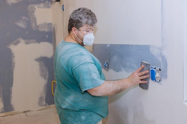 Contratista con llana de arena lijar el panel de yeso en la pared